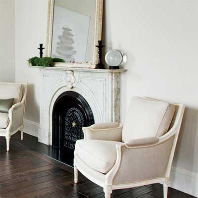the salvaged marble mantel serves as a handsome focal point that anchors a sitting area