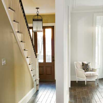 a paneled wood door with long vertical lights brightens the foyer