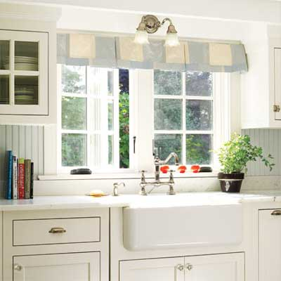 kitchen sink with window and white cabinetry