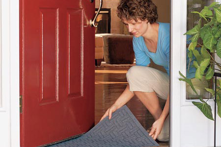 woman placing doormat on entryway floor