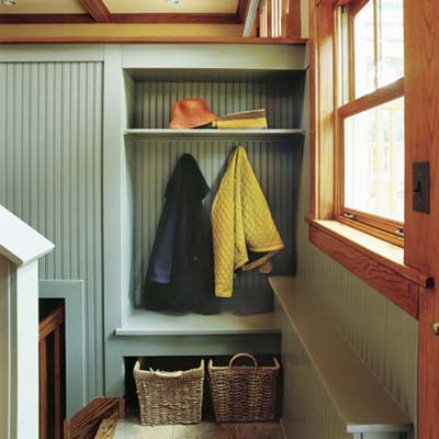 stair landing mudroom with coat hooks and storage baskets