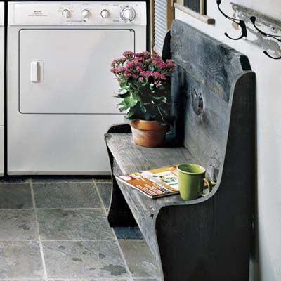 mudroom laundry area with slate floor and wood bench