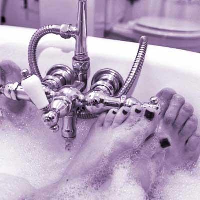 man and woman's feet in bathtub