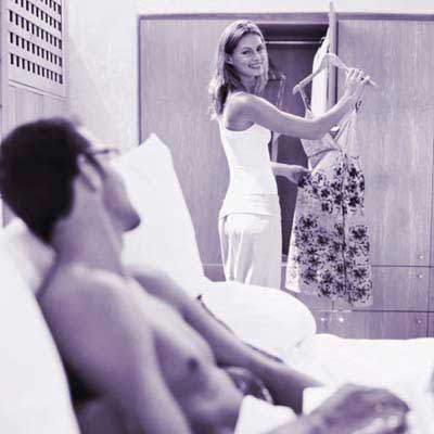 woman showing man dress in front of closet