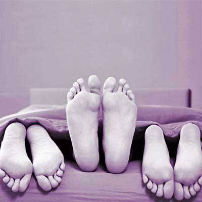 three pairs of feet poking out of sheets at the foot of the bed