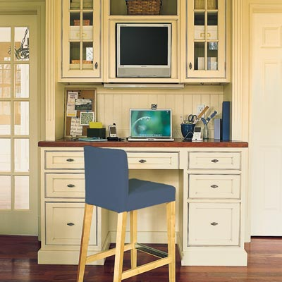 home office built into kitchen with computer and counter stool