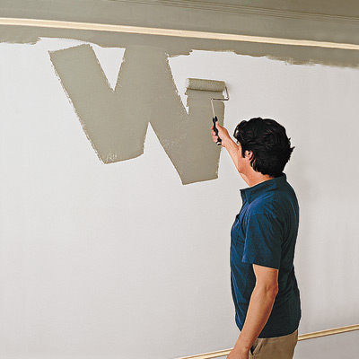 photo of man painting wall with roller