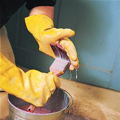hands cleaning paint brushes