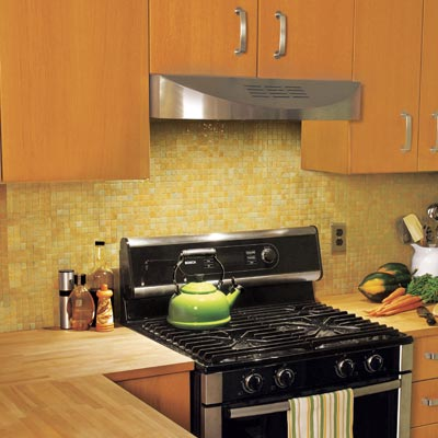 kitchen stove with yellow mosaic tile backsplash