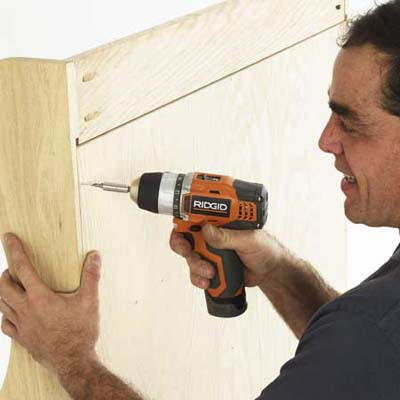 man using a drill/driver to reinforce the back of a built-in bench