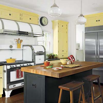 butcher block island and chrome trimmed range hood in this the italianate kitchen with yellow cabinets