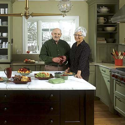 couple stands behind the island in their newly redesigned Georgian kitchen