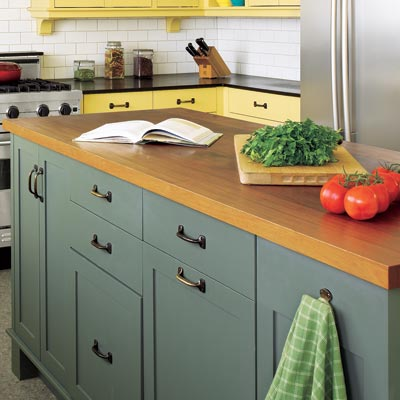 dark green island with wood butcher block top in traditional kitchen with yellow cabinets
