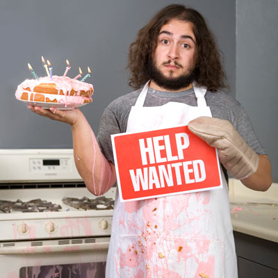 man holding help wanted sign in messy kitchen