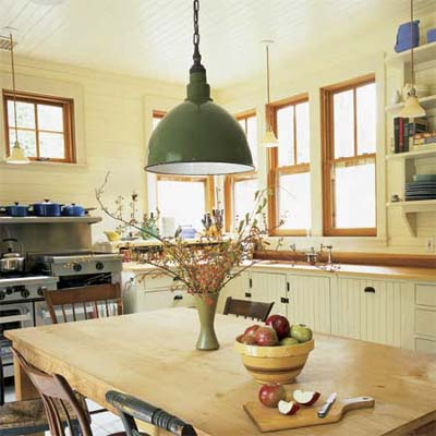 large green pendant light hanging above a rustic kitchen table