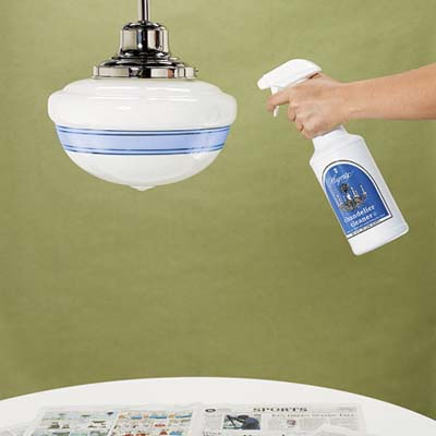 hand holding a spray bottle aimed at the glass shade of a pendant light