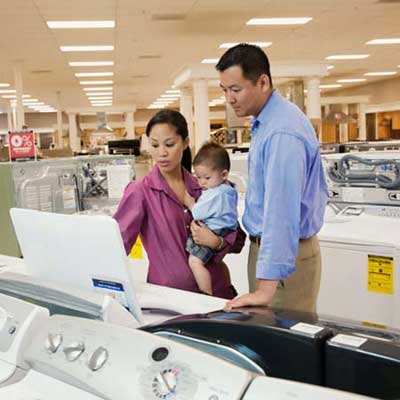two adults and an infant shopping in an appliance showroom
