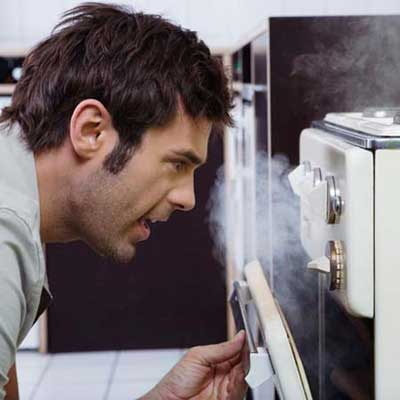 person staring into a partially open but smoking oven door
