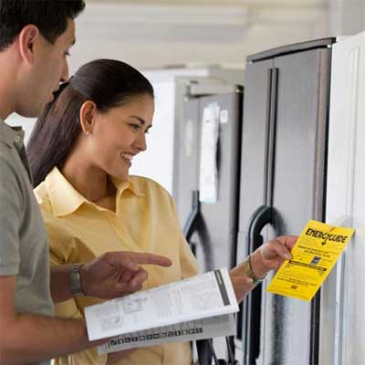 two people standing in an appliance showroom looking at a manual and energy efficiency guide