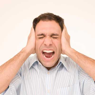 person screaming with hands clamped over their ears