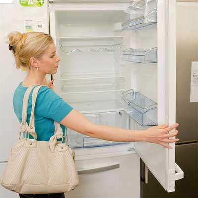 shopper examining the way a refrigerator door opens and closes