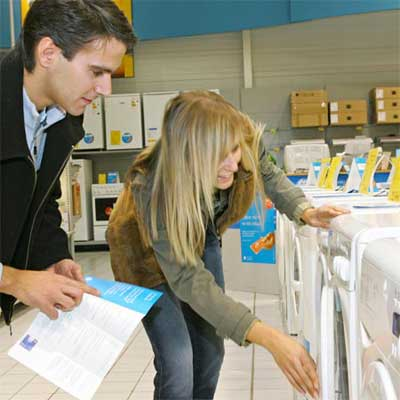 two people holding a specifications sheet and examining the front of a washer dryer