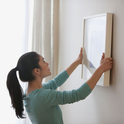 woman hanging a framed picture on the wall