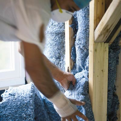 man installing recycled denim insulation batts