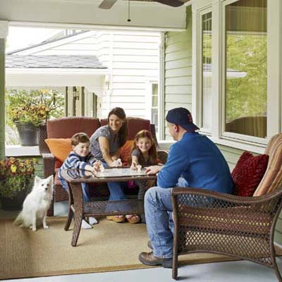 homeowners and their two kids and dog on the front porch of a newly remodeled foursquare