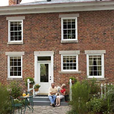 reader house remodel after: couple sitting in front of their remodeled cottage