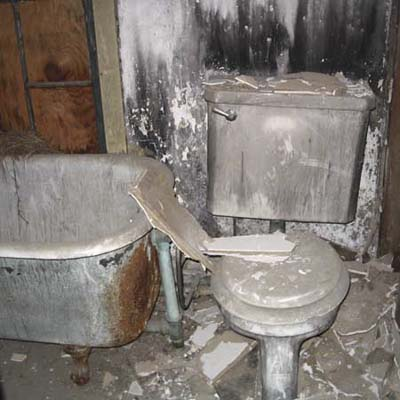 Bathroom before remodel with filthy tub and toilet