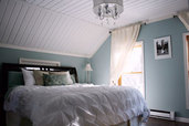 bedroom with white sloped ceiling and blue walls
