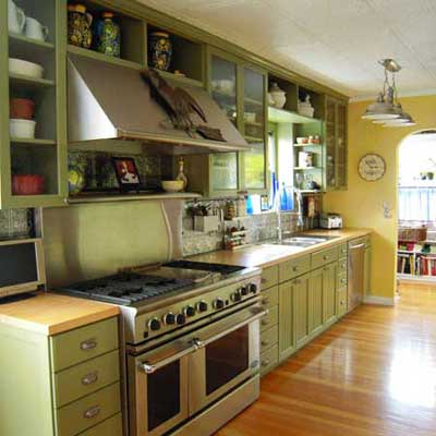 updated kitchen with green cabinets and stainless steel stove