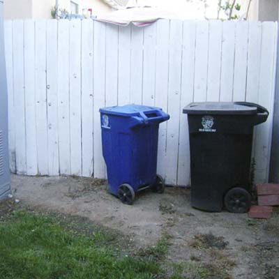 backyard fence with trash cans
