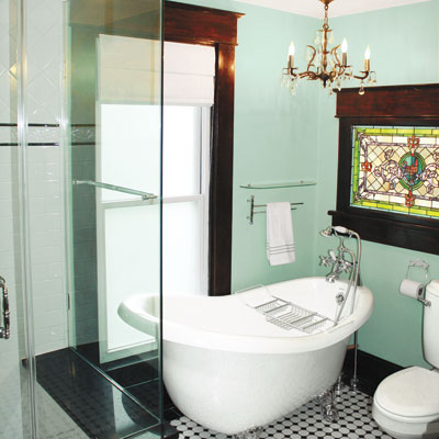 updated bathroom with stained glass window, chandelier and claw foot tub