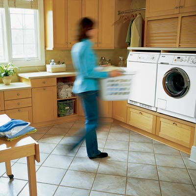 woman carrying laundry basket in laundry room
