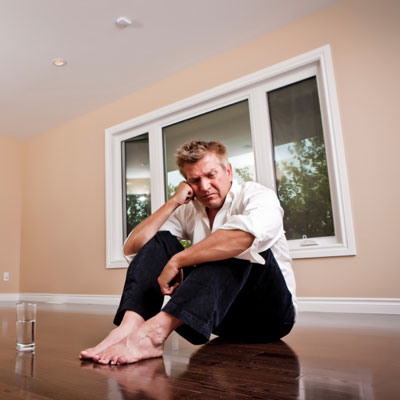 man sits barefoot on a hardwood floor next to glass of water, looking regretful