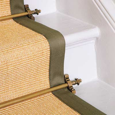 a detail of a stair runner secured by an oli-rubbed bronze runner rod