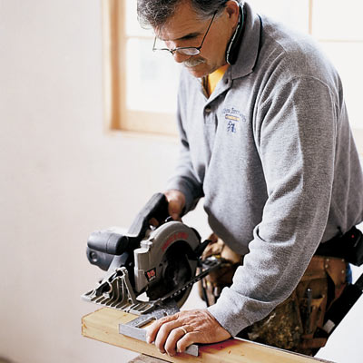 man using speed square to guide circular saw