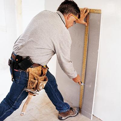 man using drywall square to cut drywall