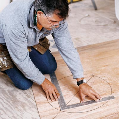 man using framing square to find center of circle