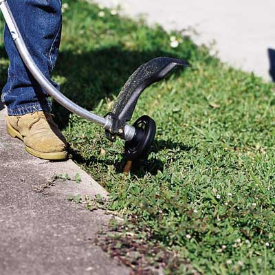 man using string trimmer to edge