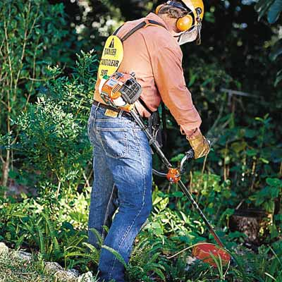 man with safety equipment using string trimmer to cut brush