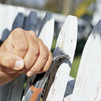 hand scraping paint off fence