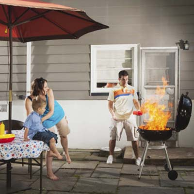 woman and child afraid as man adds lighter fluid to flaming grill 