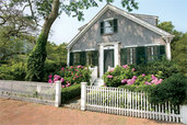 beautiful white picket fence in front of a house and flower garden
