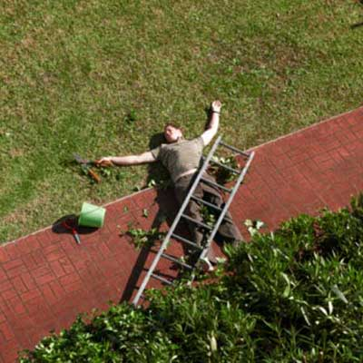 man lying on ground after falling off ladder