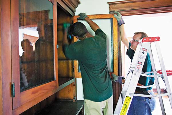 crew members slicing through multiple coats of paint to remove built-in cabinetry