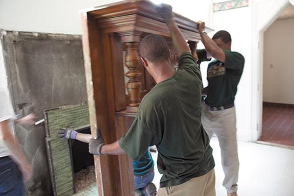 crew members removing fireplace mantel