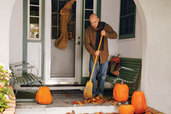 sweeping leaves at the front entryway